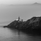 Closeup of the lighthouse.. Boat is entering the fog of the background.